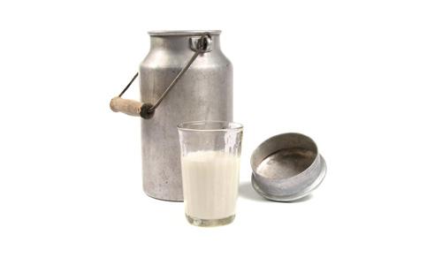 Mleko w szklance obok bańki na mleko